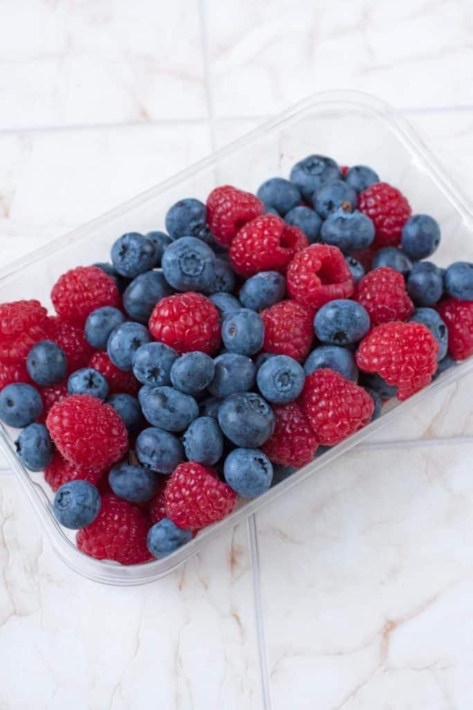 A plastic container full of blueberries and raspberries
