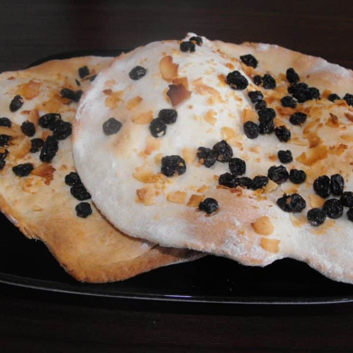 Two Peshwari Naan breads on a black plate
