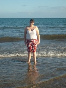 Dannii standing on a beach wearing a white vest and red shorts