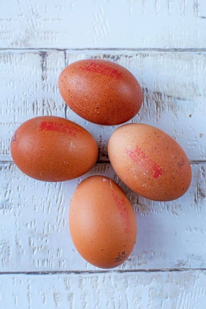 Four unbroken eggs on a wooden background