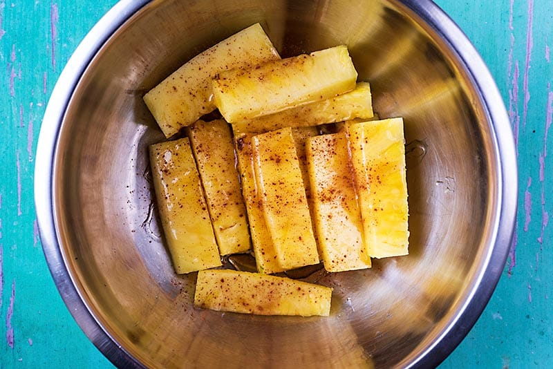A mixing bowl containing sticks of pineapple covered in honey and cinnamon