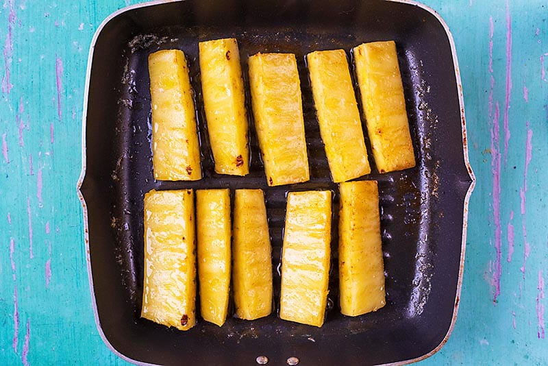 A griddle pan with pineapple sticks on it