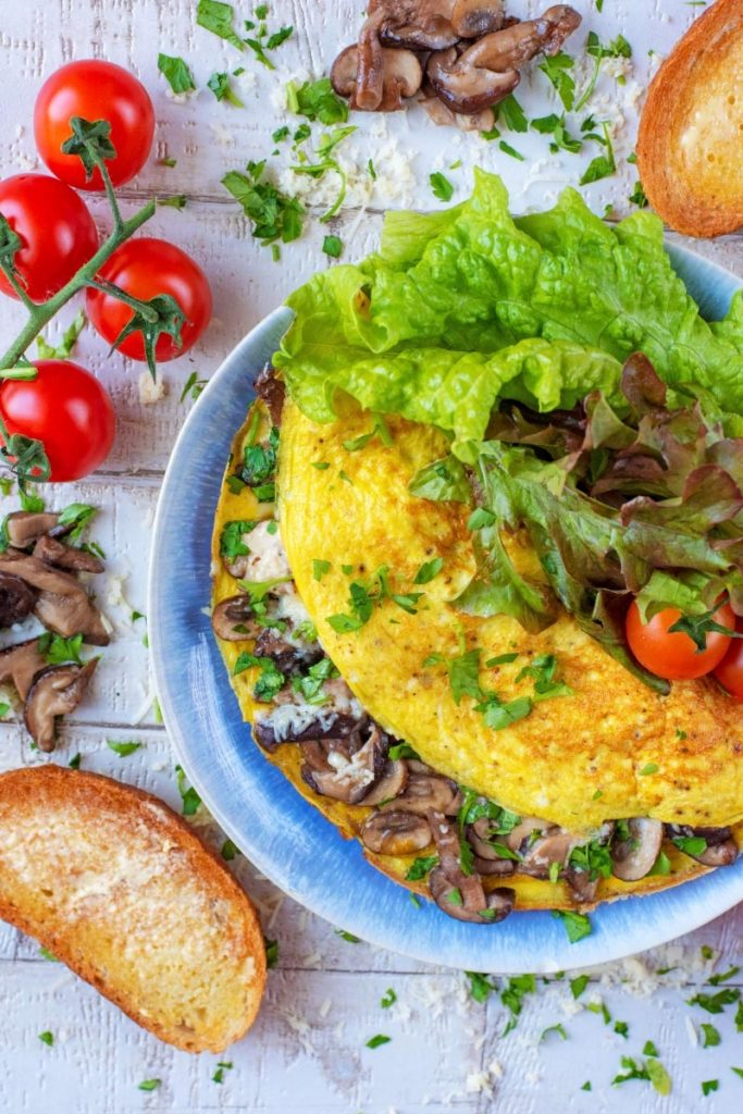 A mushroom omelette on a plate with salad