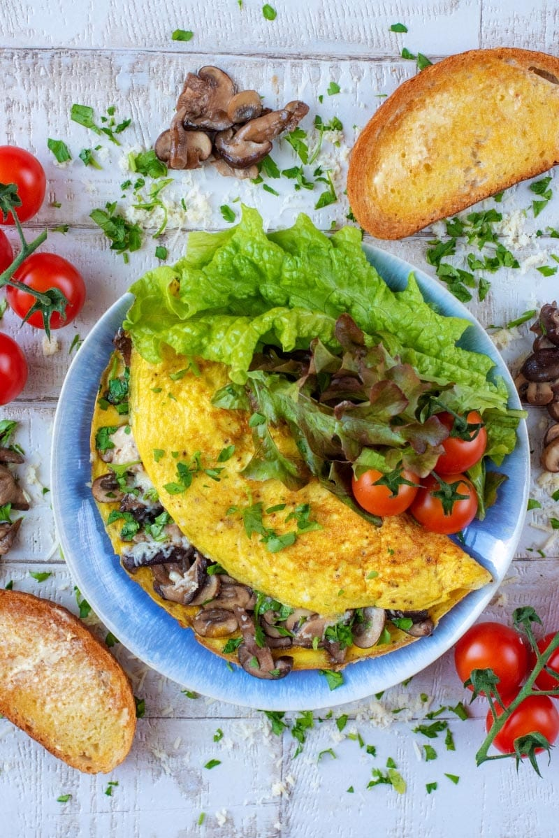 Mushroom omelette and salad on a plate with bread and tomatoes