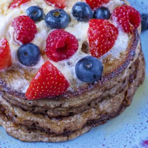 A stack of pancakes with berries and cream on top