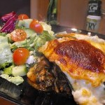 Seafood Lasagna on a black plate with some salad