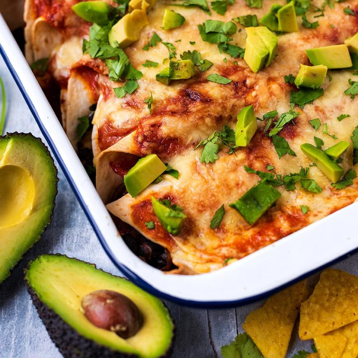 A baking dish filled with bean and vegetable enchiladas