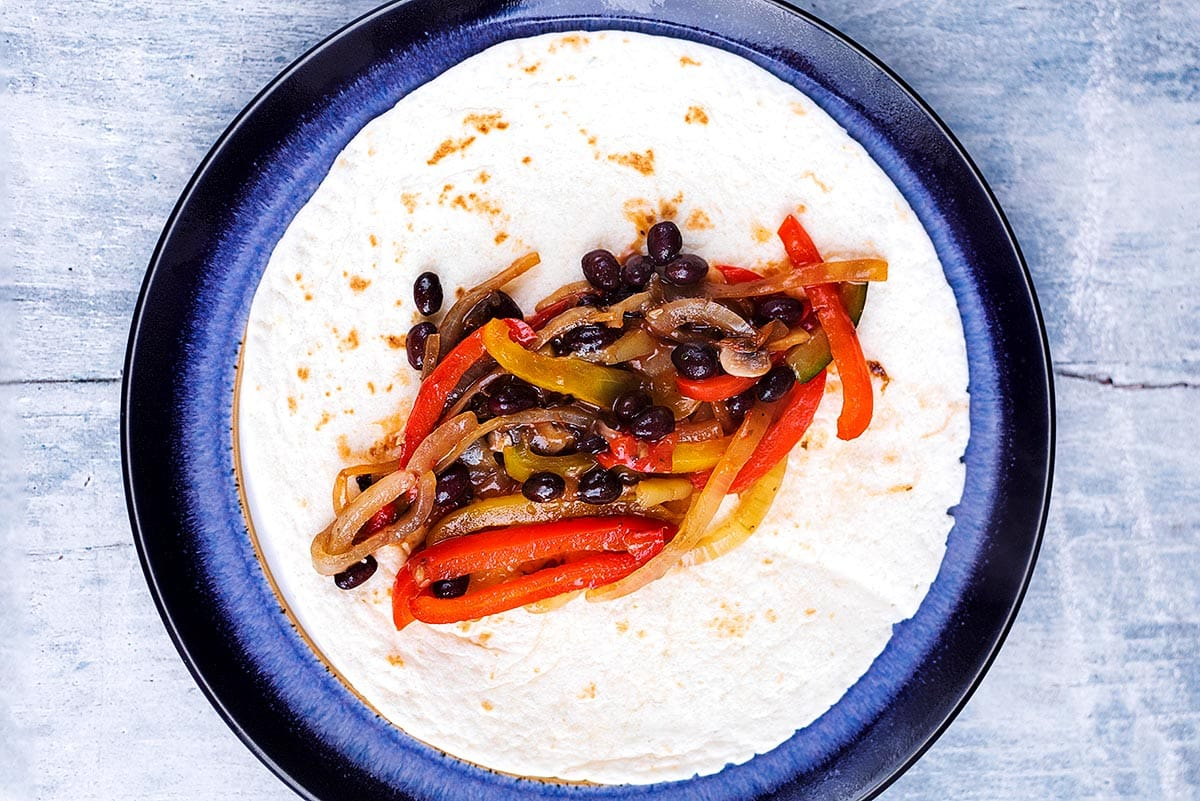 A flour tortilla with cooked beans and sliced vegetables along the middle of it