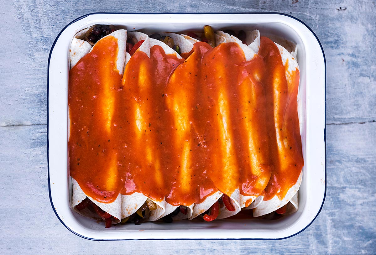 Enchiladas in a baking dish smothered with sauce