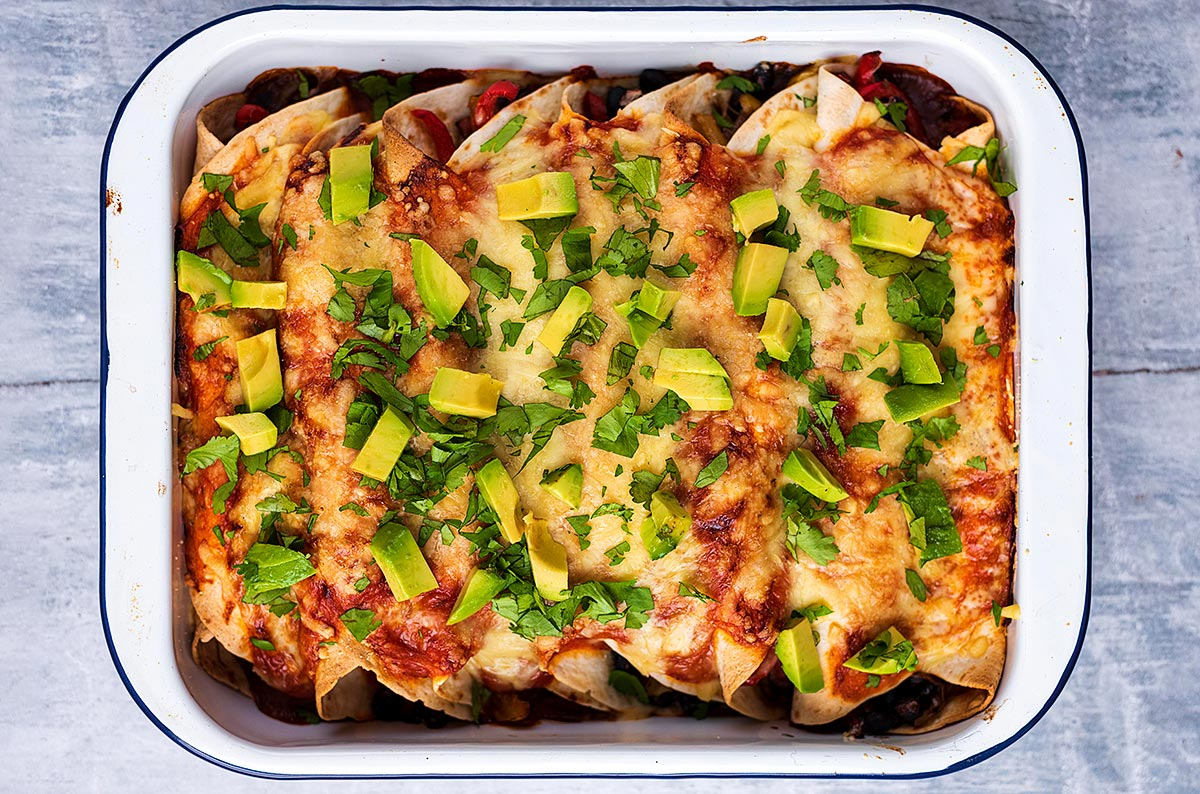 Cooked enchiladas topped with herbs and avocado cubes