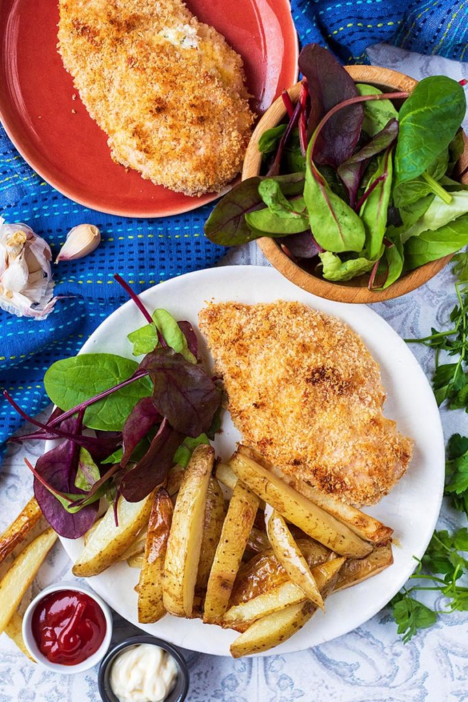 A chicken Kiev on a plate with some fries and a salad. Two pots of sauce sit next to the plate