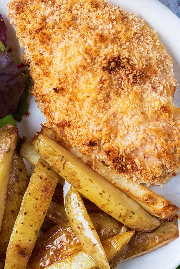 A baked chicken Kiev on a plate with some potato fries