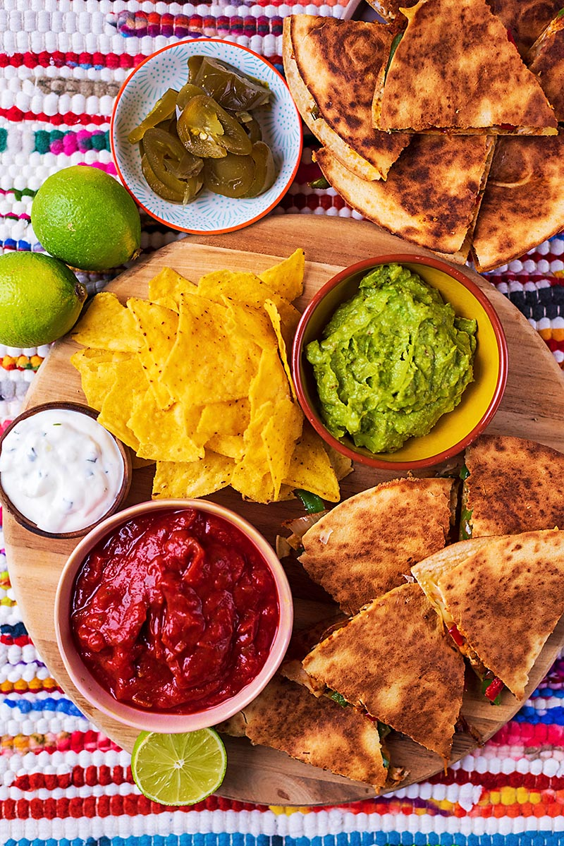 Chicken Quesadillas set out with tortilla chips, dips, pickled jalapenos and lime wedges