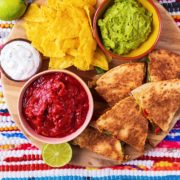 Slices of chicken quesadilla on a serving board with tortilla chips, salsa and guacamole