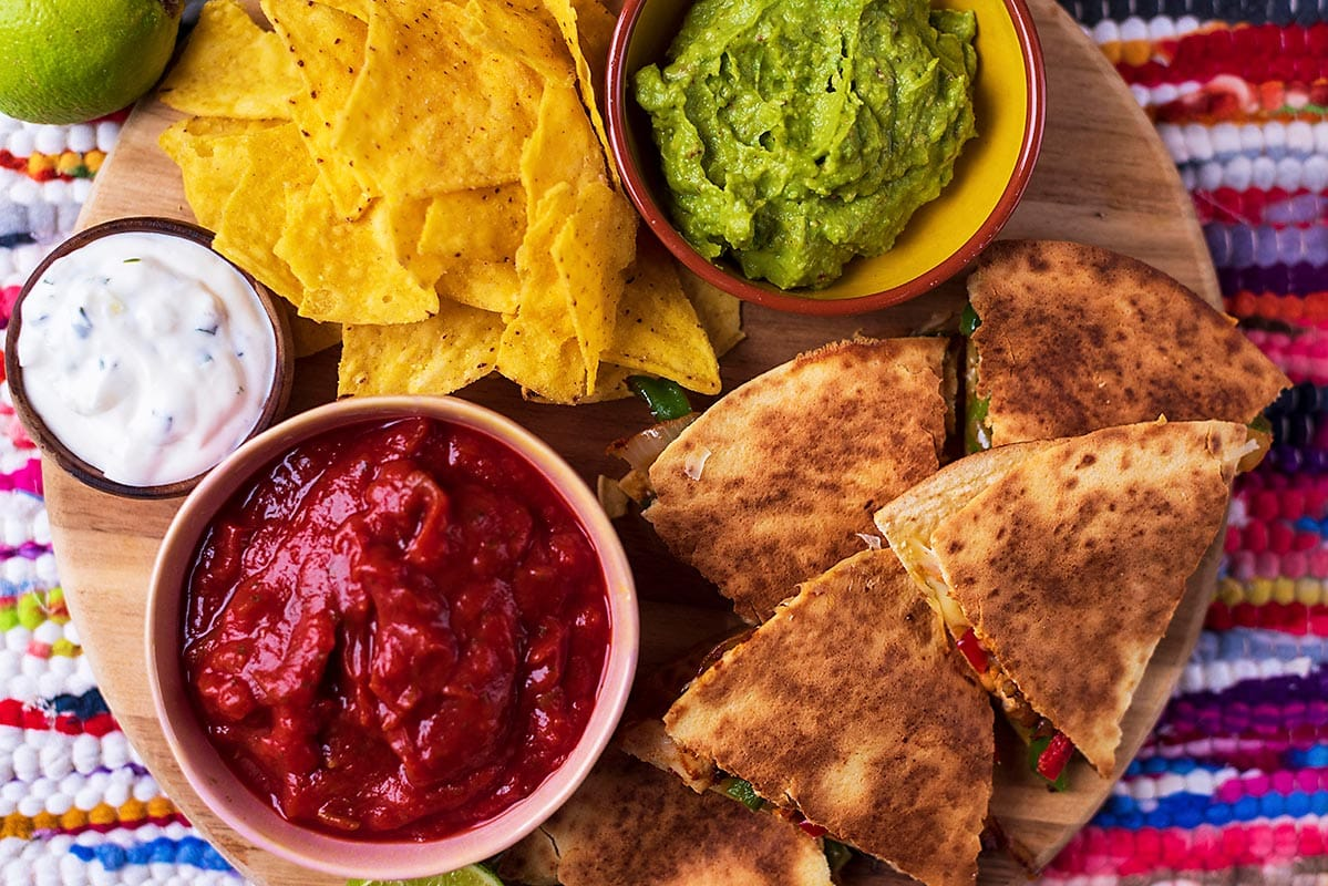 A board full of quesadillas on a colourful table cloth