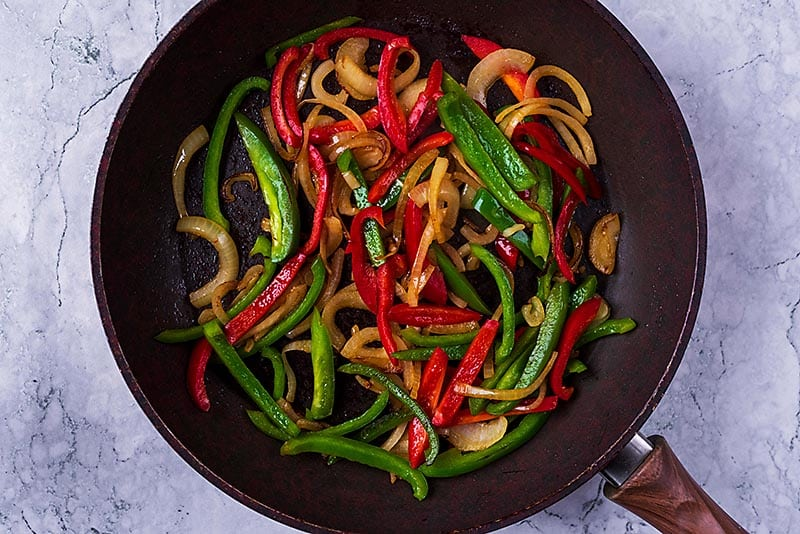 Sliced peppers and onions cooking in a frying pan