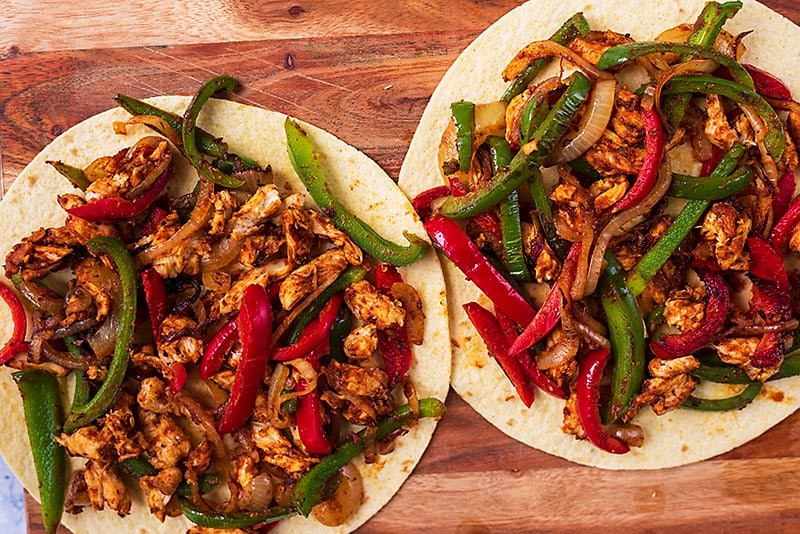 Two flour tortillas covered in cooked and seasoned chicken and vegetables