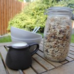 Homemade muesli in a jar next to bowls and a jug of milk