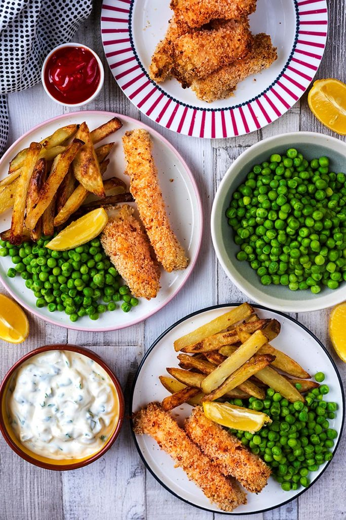 Two plates with fish sticks, fries and peas next to a bowl of tartar sauce