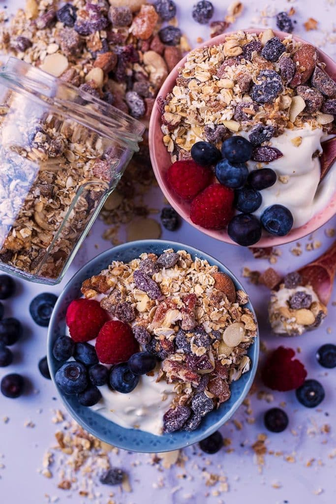 Two bowls of yogurt topped with muesli and berries