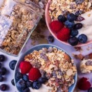 Two bowls of yogurt topped with homemade muesli and berries