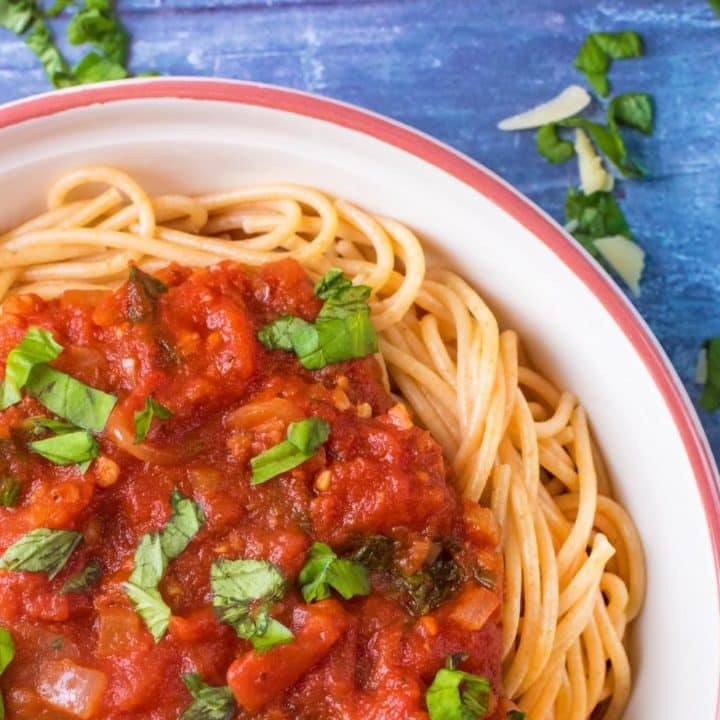 A plate of spaghetti covered in Marinara and chopped herbs