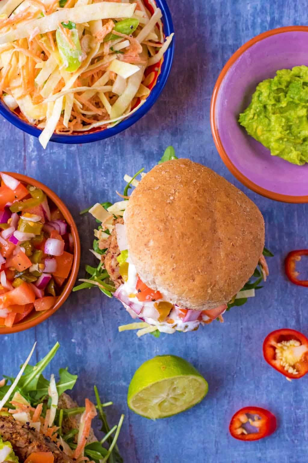 A burger in a bun next to a dish of guacamole, salsa and coleslaw