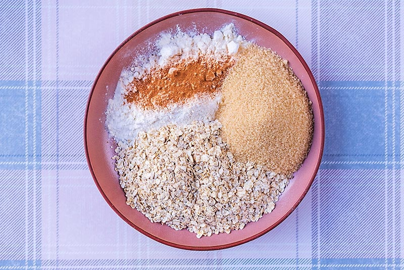 Oats, cinnamon, flour and brown sugar together on a plate