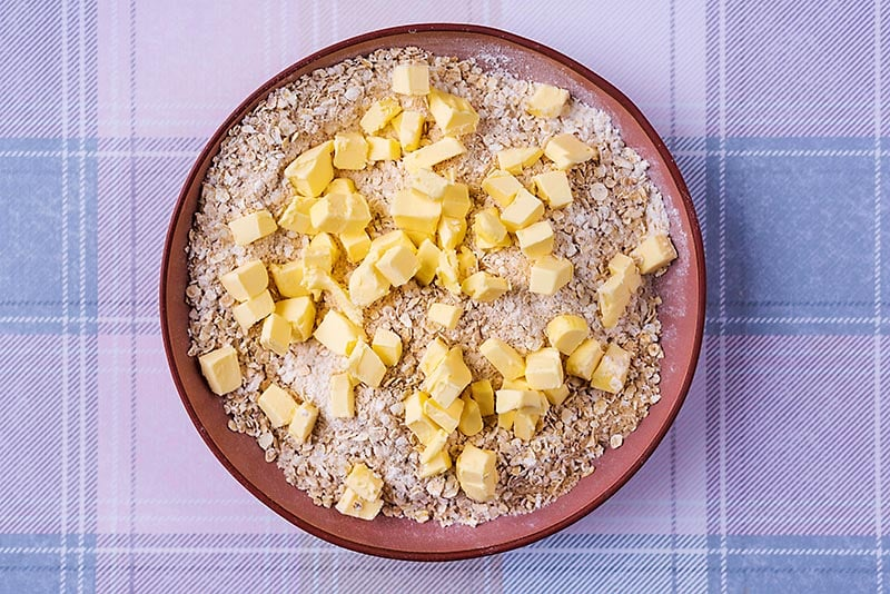 Oats, sugar and flour mixed together with cubes of butter
