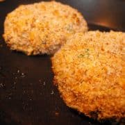 Two salmon fishcakes on a black plate