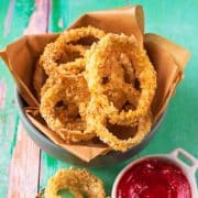 A bowl of baked onion rings next to a small pot of ketchup