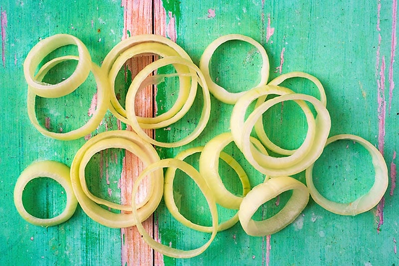An onion cut into rings on a green wooden surface