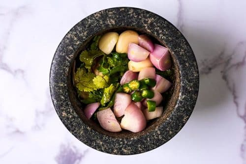 A mortar bowl containing Thai curry paste ingredients