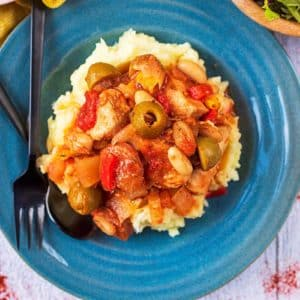 Slow Cooker Spanish Chicken on a blue plate with a fork and spoon