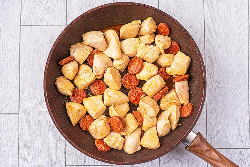 A frying pan containing chunks of chicken and slices of chorizo