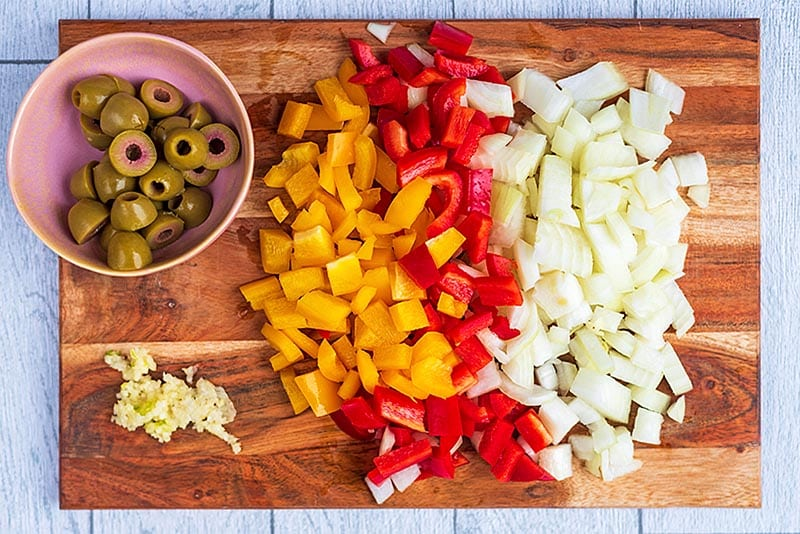 A wooden chopping board with chopped onion, red and yellow pepper, green olives and minced garlic