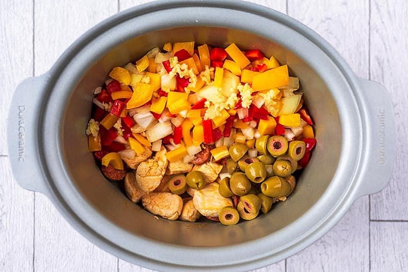 A slow cooker pot containing chicken, chorizo and chopped vegetables