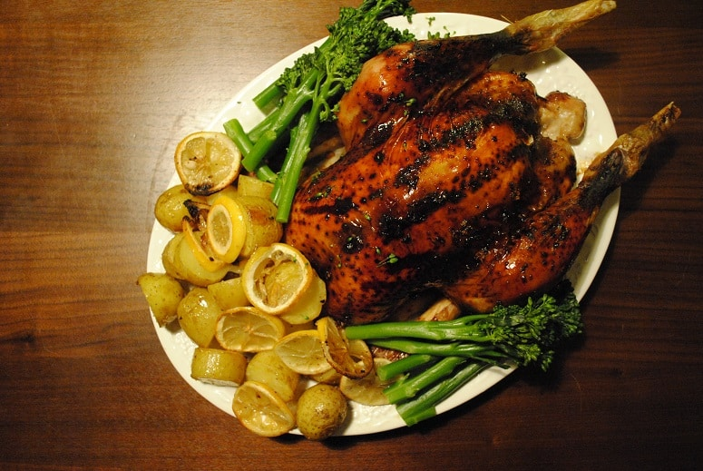 Roast Chicken on a white serving plate with asparagus and potatoes