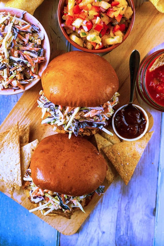 Two brioche buns with pulled pork and slaw sat on a wooden board