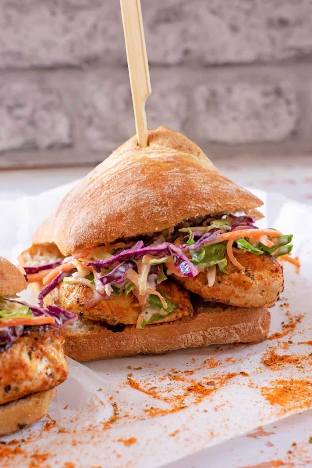 Chicken Burger and slaw in a bun with a wooden skewer through it all