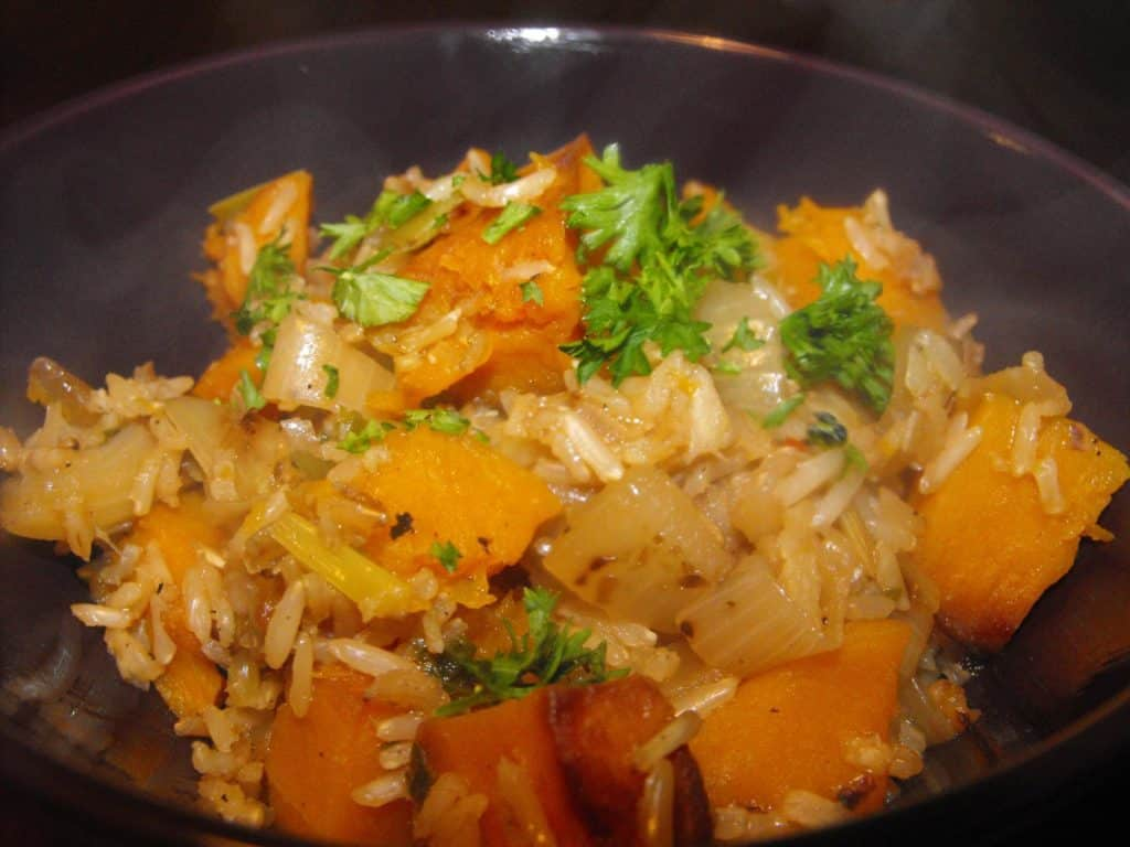Butternut squash risotto in a purple bowl topped with chopped parsley