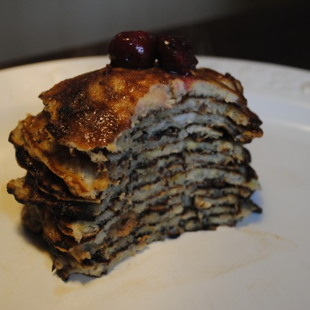 Flourless pancakes piled up with cherries on top