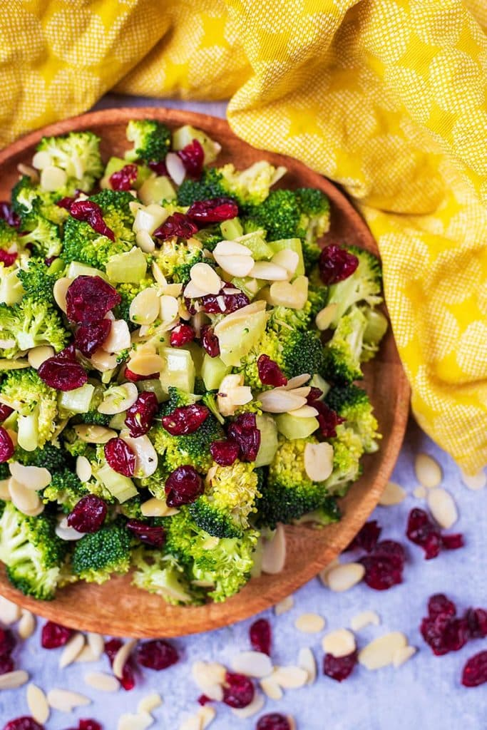 A salad of raw broccoli, cranberries and almonds on a wooden plate