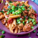 Cajun Chicken Pasta topped with sliced green onions, on a pink plate