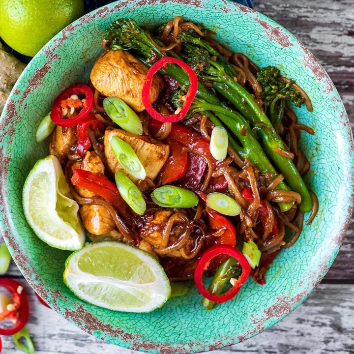 Chicken Pad Thai in a green bowl with two lime wedges