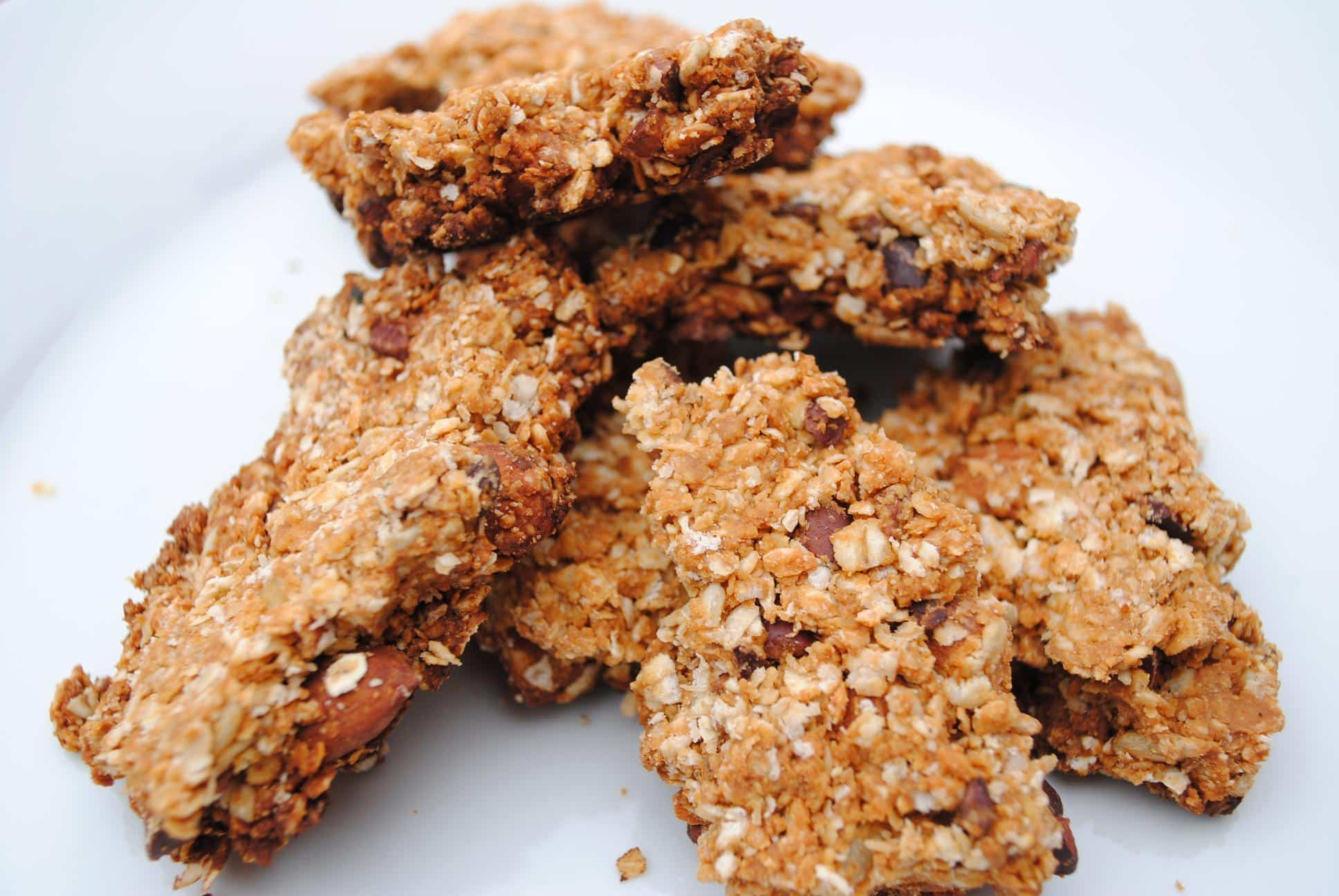 Homemade granola bars piled up on a white plate