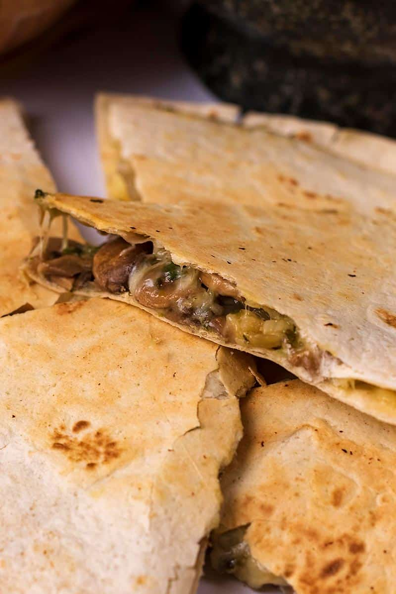 A stack of quesadilla slices with one showing the filling