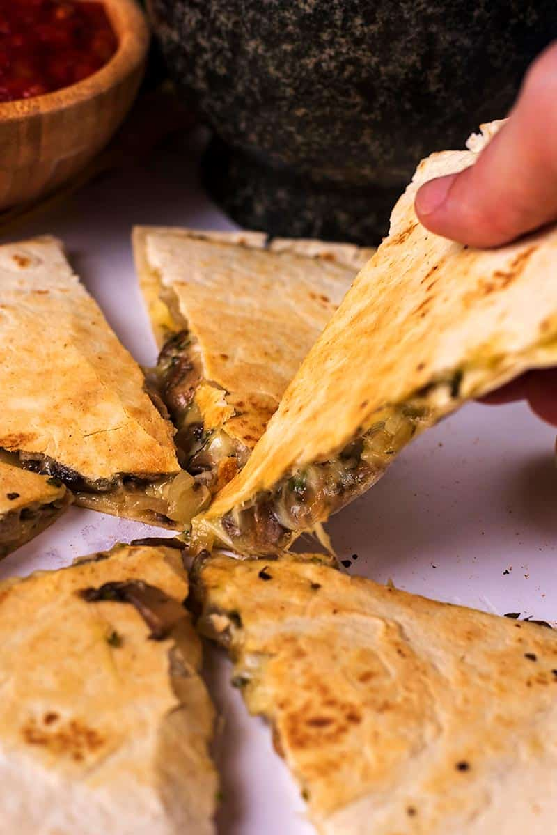 A quesadilla cut into slices with one slice being picked up