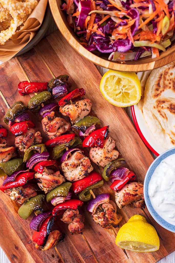 Chicken chunks and diced vegetable skewers on a wooden board