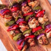Four marinated chicken skewers on a chopping board